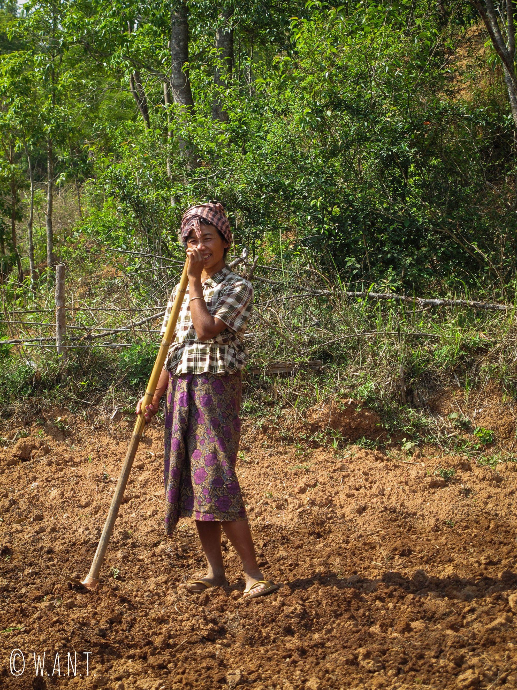 Jeune femme souriante malgré le travail difficile dans les champs