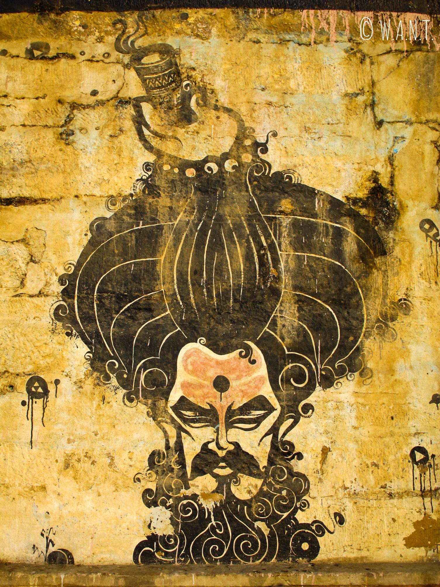 Art de rue - tête de Sadhu sur le mur d'un Ghat