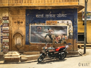 Moto garée devant une affiche de film indien dans les rues de Jaisalmer