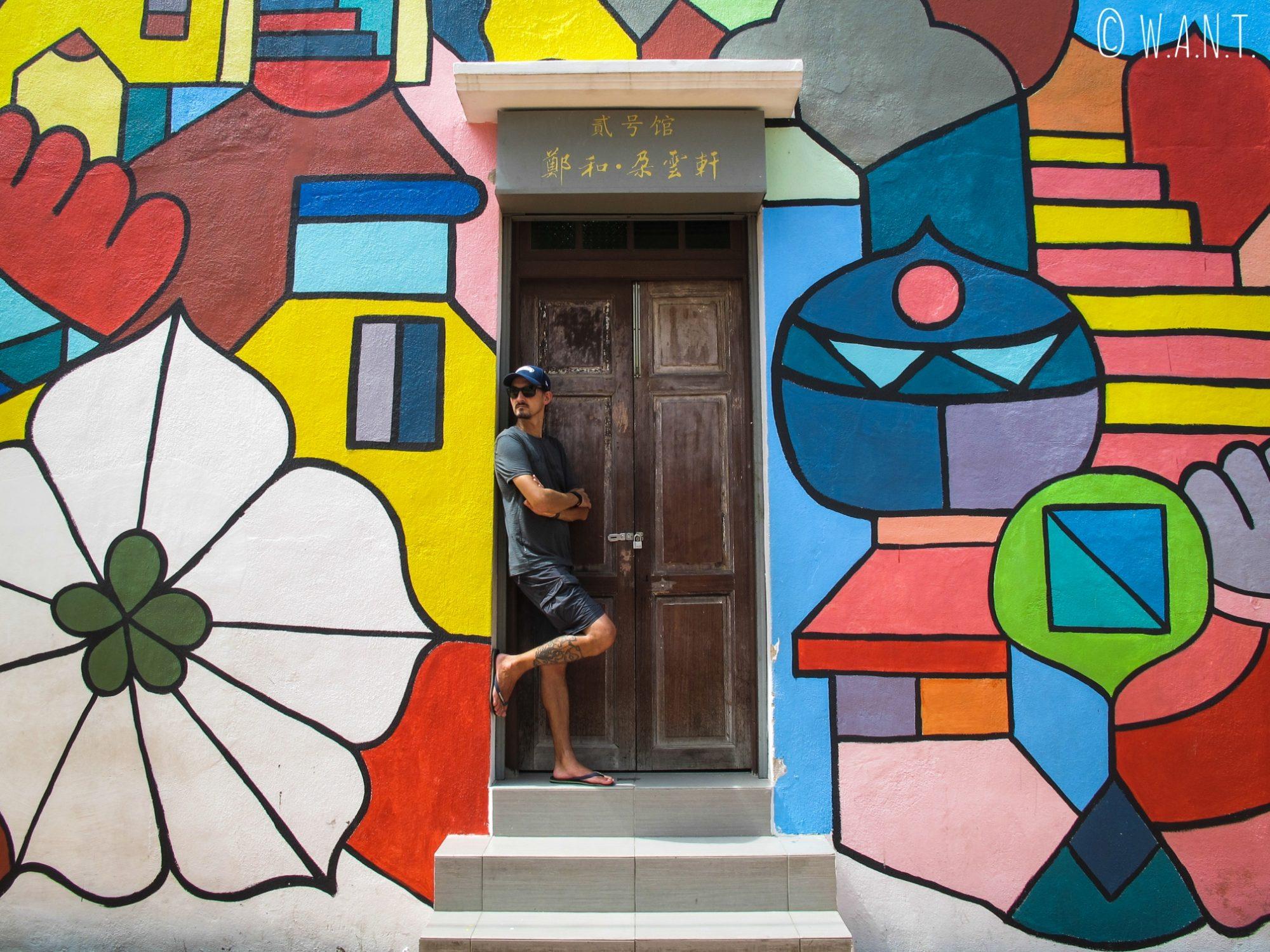Benjamin apprécie l'art de rue qui recouvre les façades des maisons au bord de la rivière de Malacca