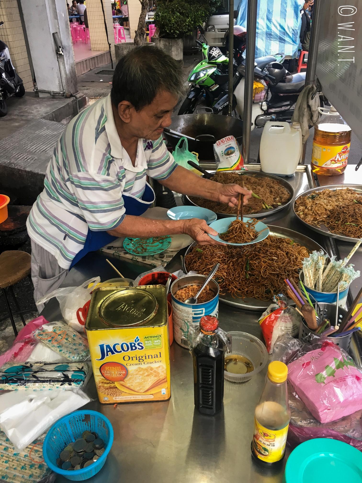Ce vieil homme cuisine de délicieuses nouilles sur son stand installé rue Kimberley street à Penang