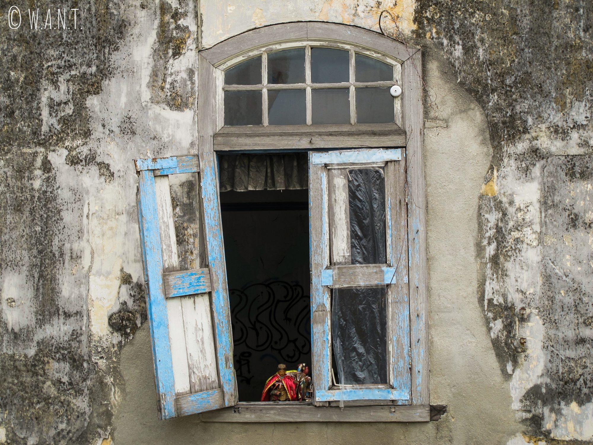 Volet branlant sur façade délabrée de Malacca