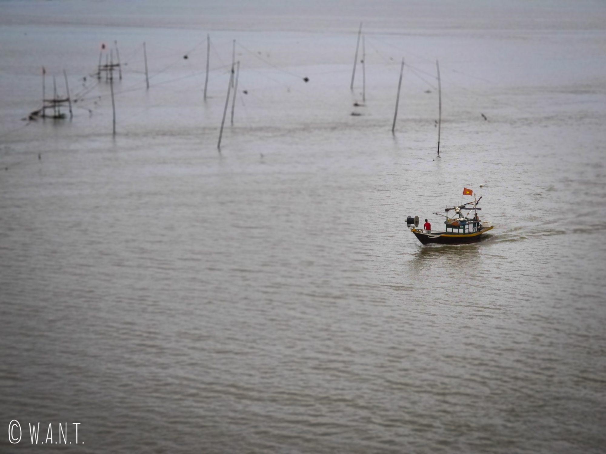 Bateau de pêche naviguant dans l'estuaire de Hoi An