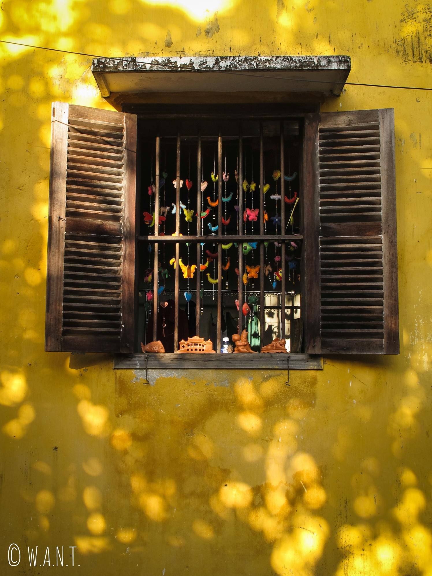 Fenêtre d'une bâtisse jaune de la vieille ville de Hoi An