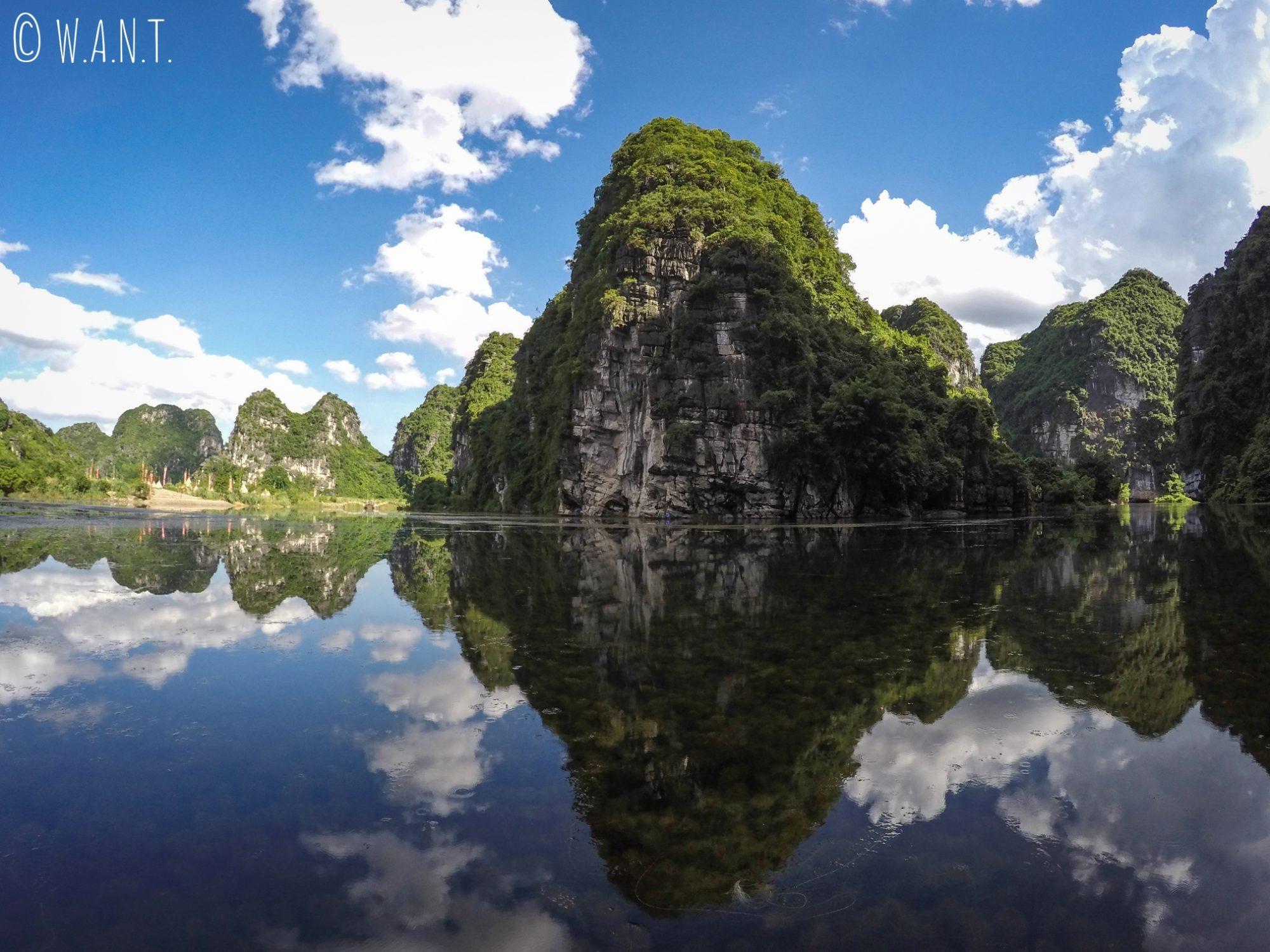 Reflets sur l'eau des pics karstiques à Trang An
