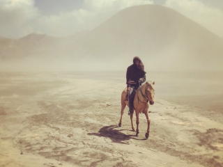 Cavalier à travers la poussière de la caldeira du volcan Bromo