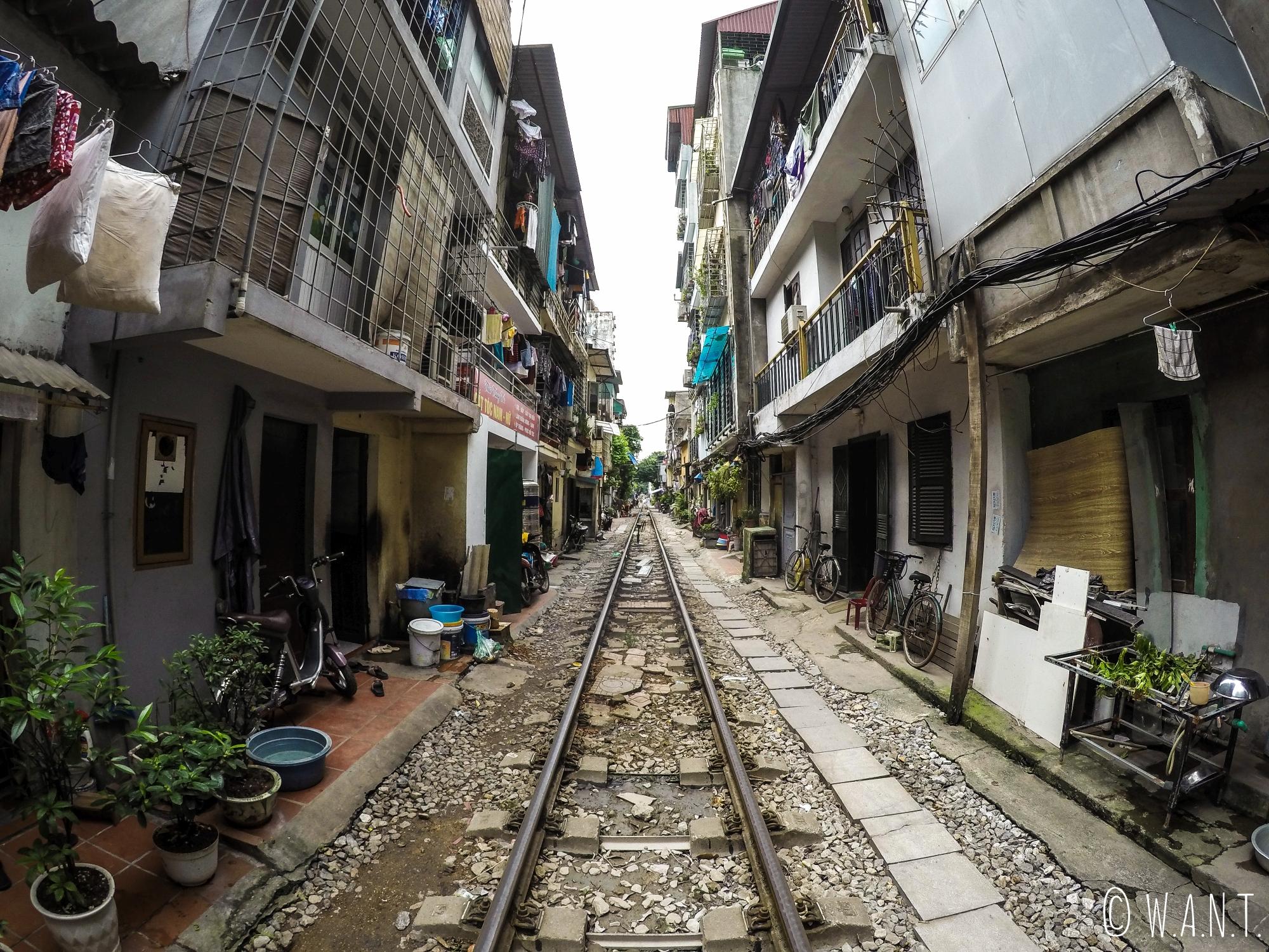 Le train passe entre les habitations à Hanoï