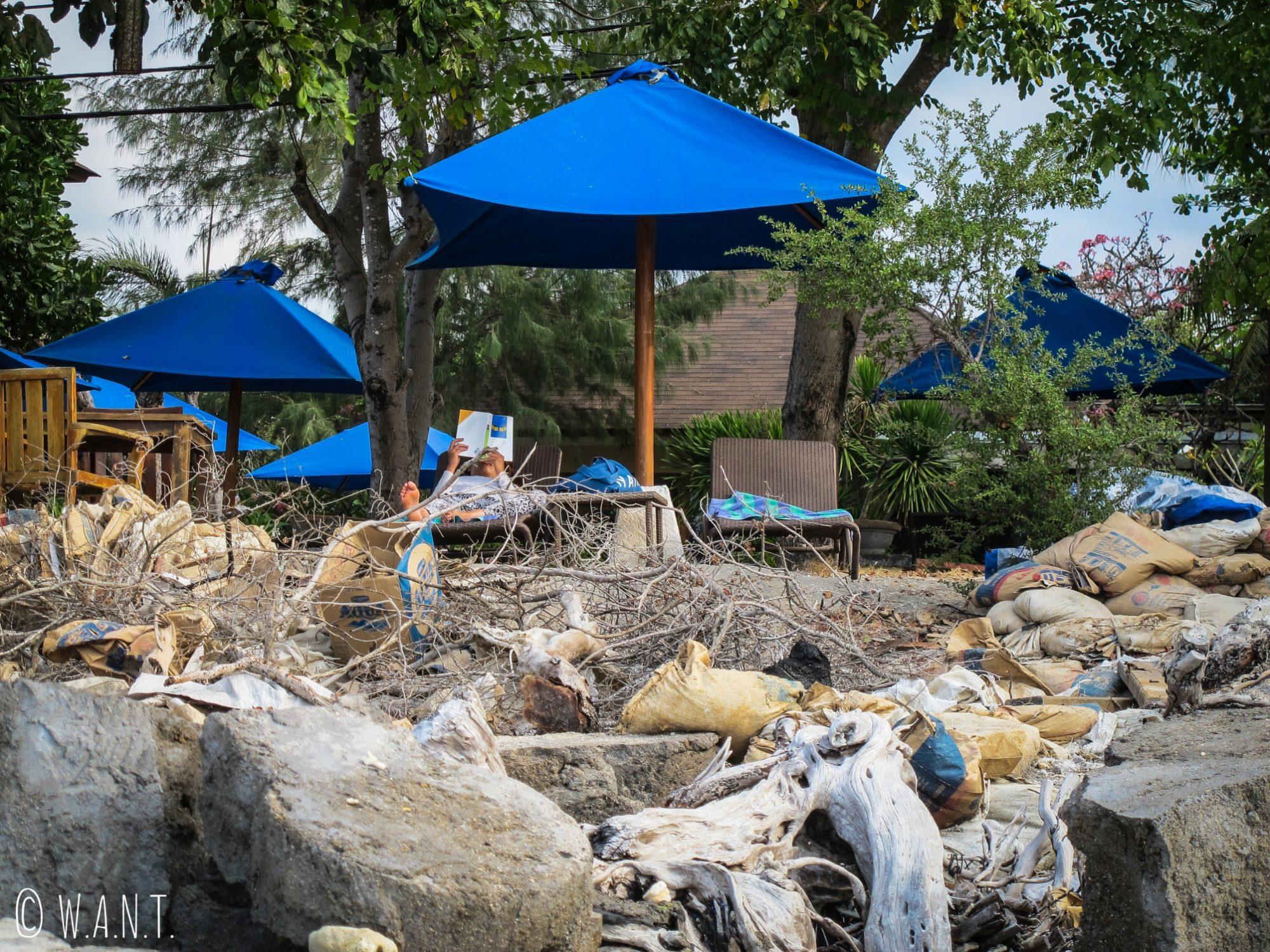 Transats et parasols devant un amas de déchets sur Gili Trawangan