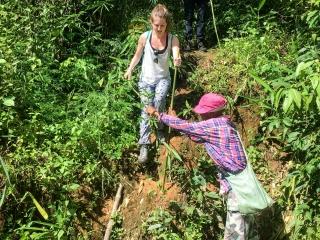 Notre guide, Dam, nous aide à traverser sur des bambous durant notre trek à Chiang Rai
