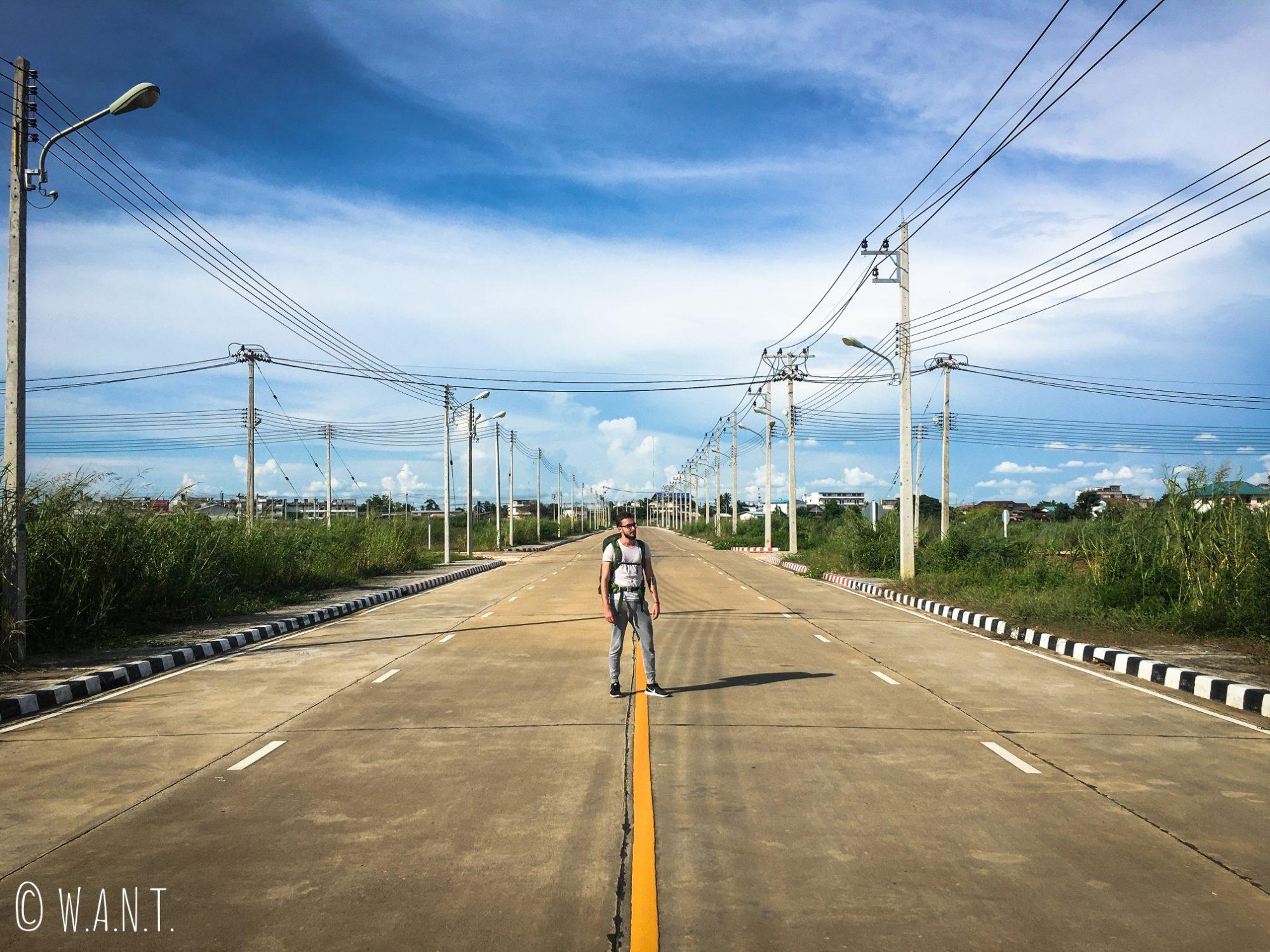Thomas sur la route déserte de la gare de bus de Sukhothai