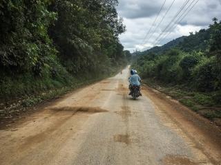 Agnès et Jilles de dos, sur une portion de route entre Luang Namtha et Muang Sing