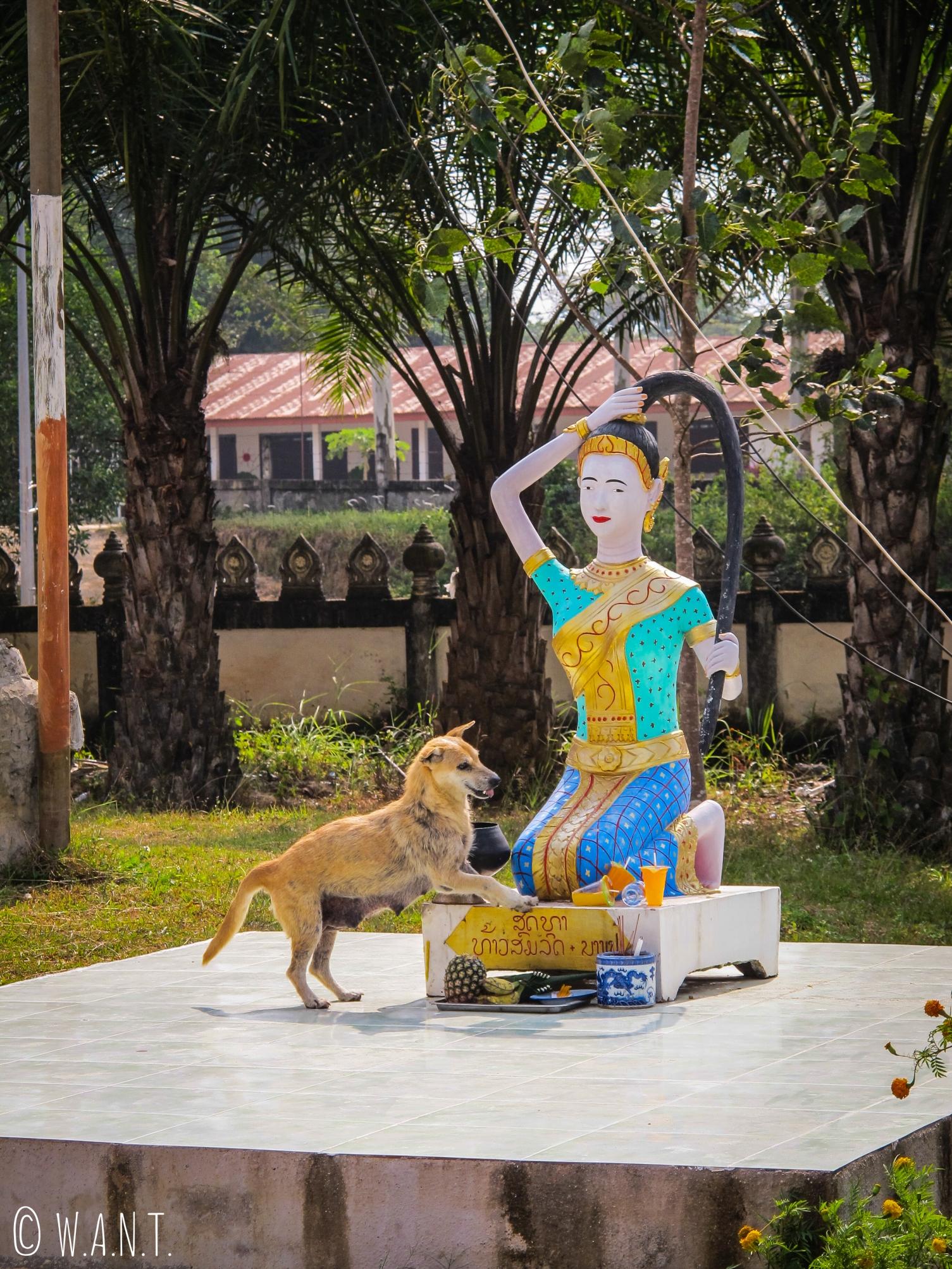 Chien au pied d'une statue dans le temple de Lak Sao
