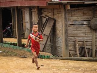 Enfant en train de courir dans un village près de Luang Namtha au Laos