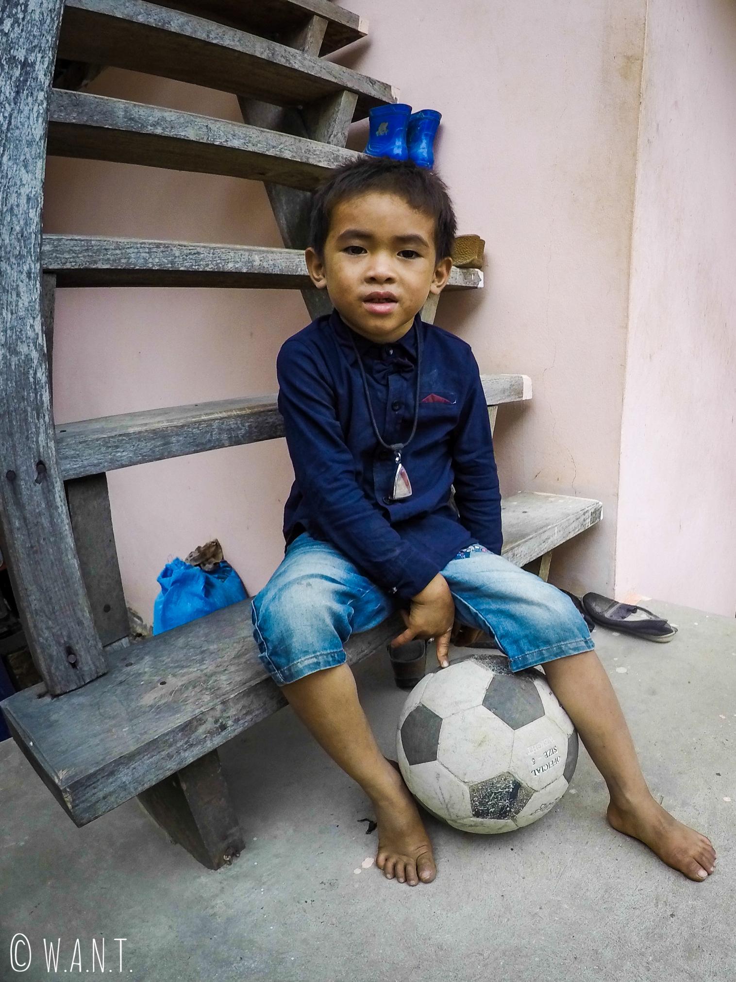 Enfant jouant au ballon dans le village de Konglor