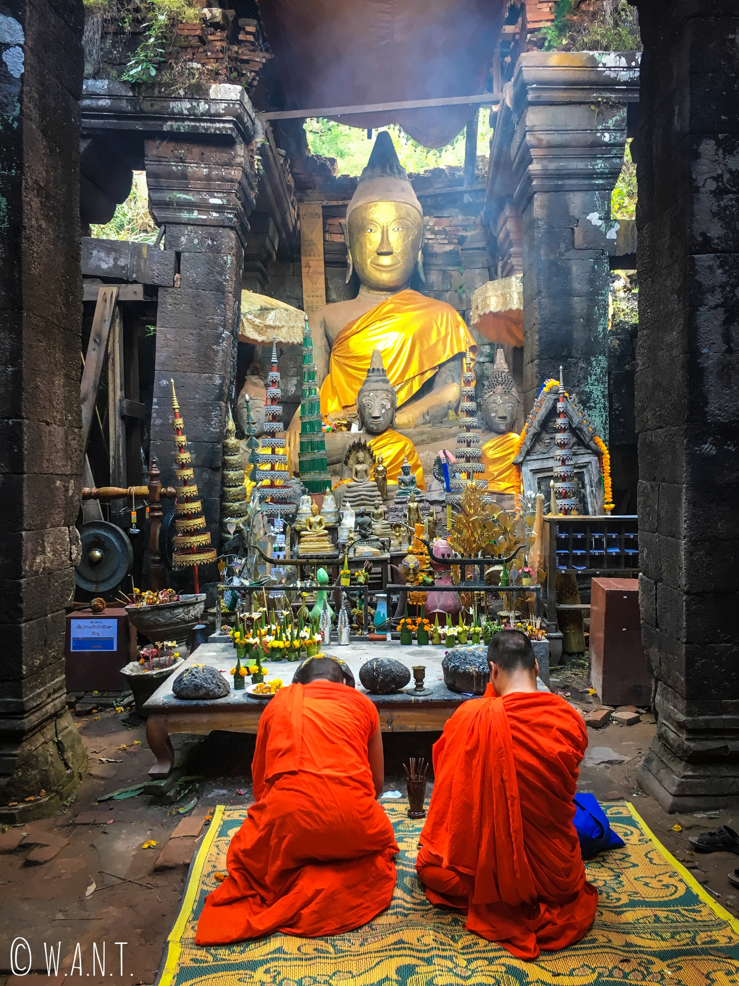 Moines se recueillant devant une statue de Bouddha sur le sanctuaire de Vat Phou