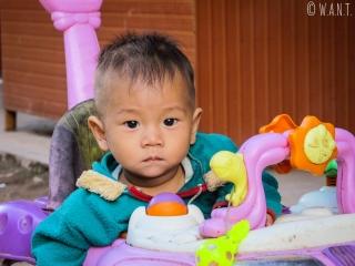 Portrait d'un enfant jouant dans les allées du marché de Muang Sing