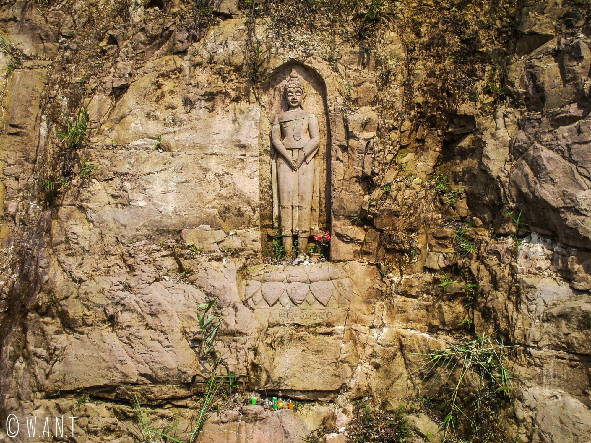 Statue de Bouddha gravée dans la roche sur le bord de la route de la boucle de Thakhek