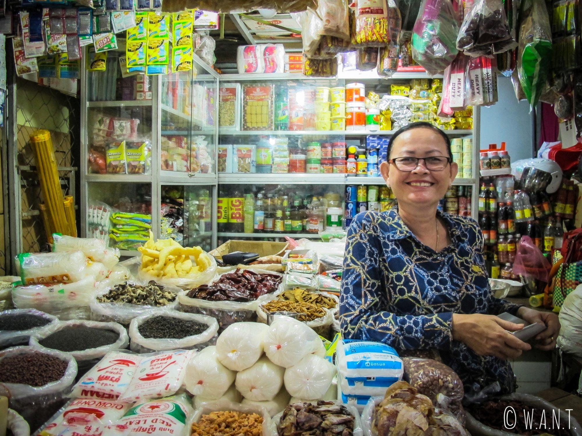 Commerçante souriante et son étal au marché couvert de Kratie