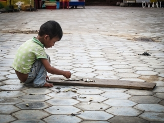 Enfant ramassant les poissons tombés sur le sol à Kep