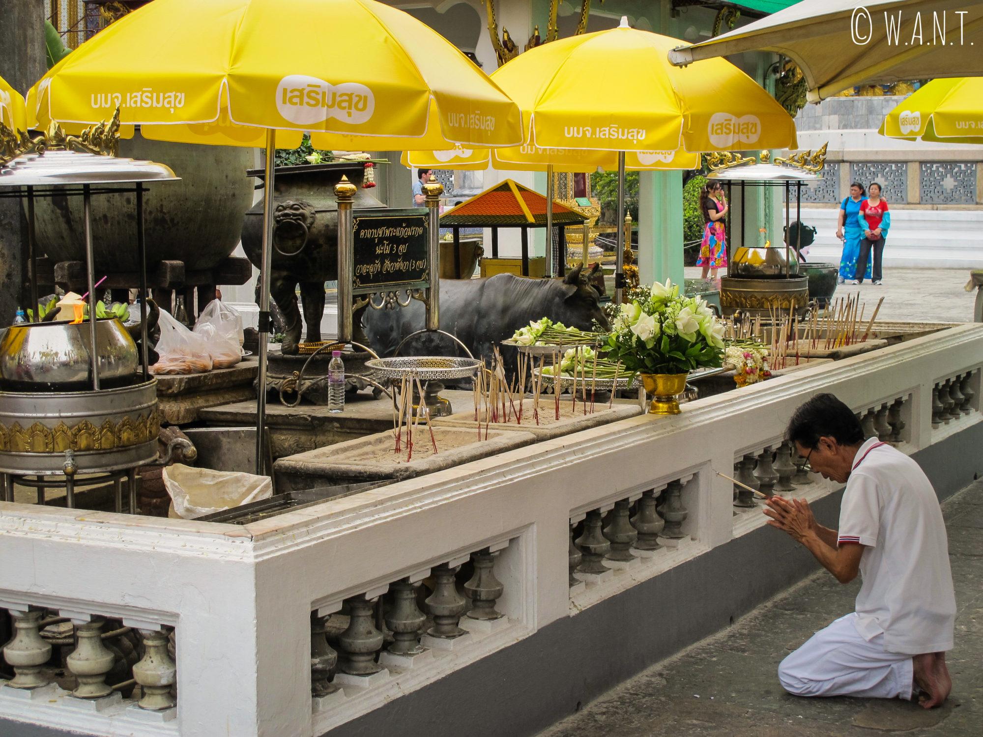 Homme effectuant la prière en arrière du temple principal du Palais Royal de Bangkok