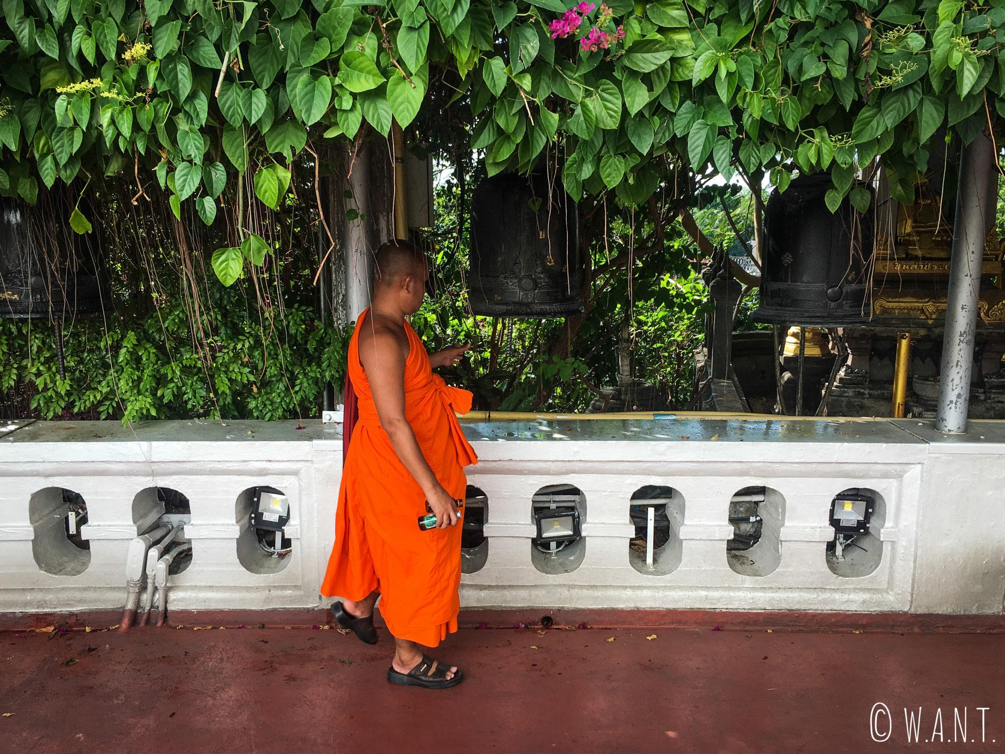 Moine faisant retentir les cloches au Golden Mount de Bangkok