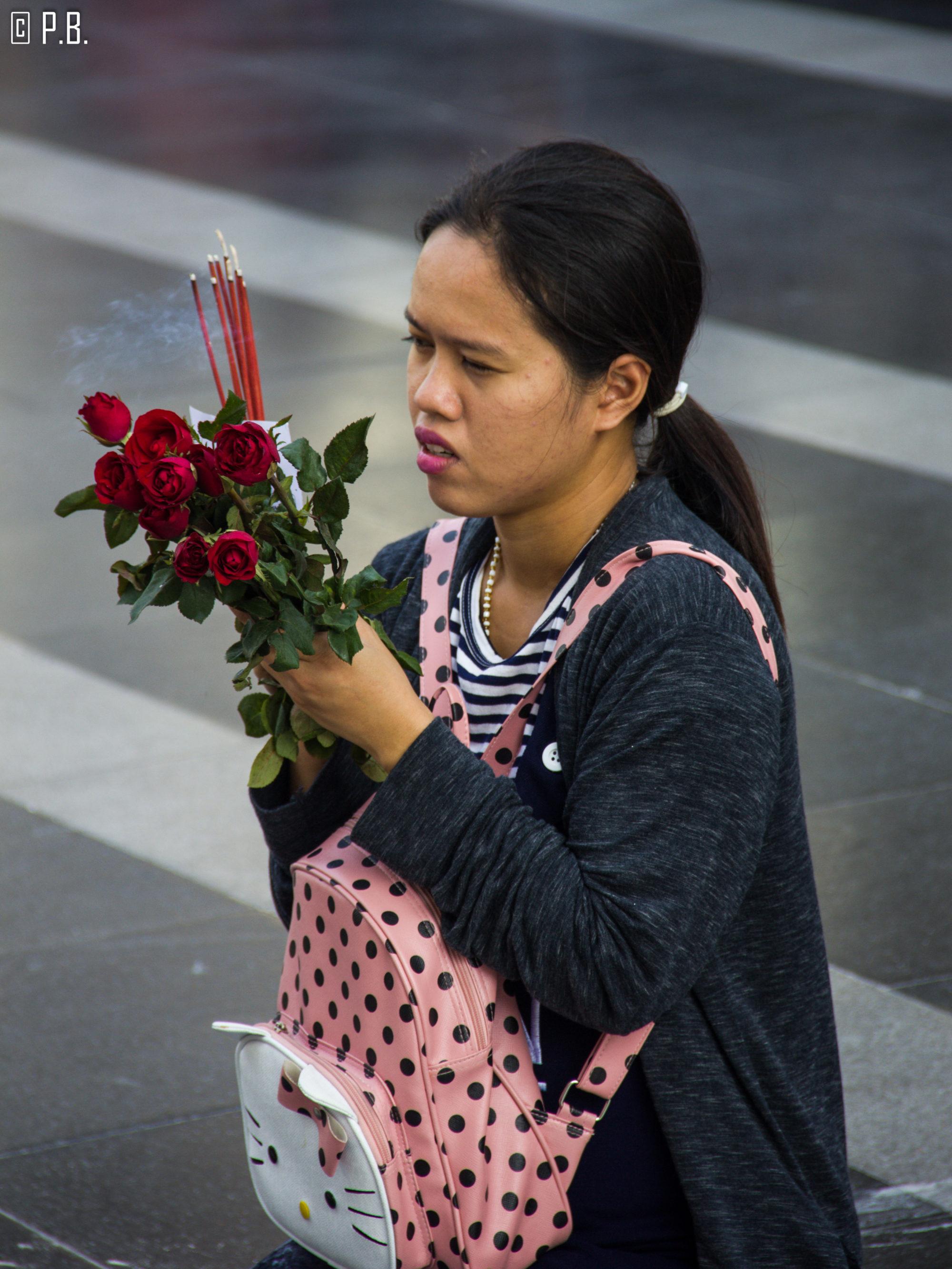 Portrait d'une jeune femme se recueillant devant une maison aux esprits de Bangkok