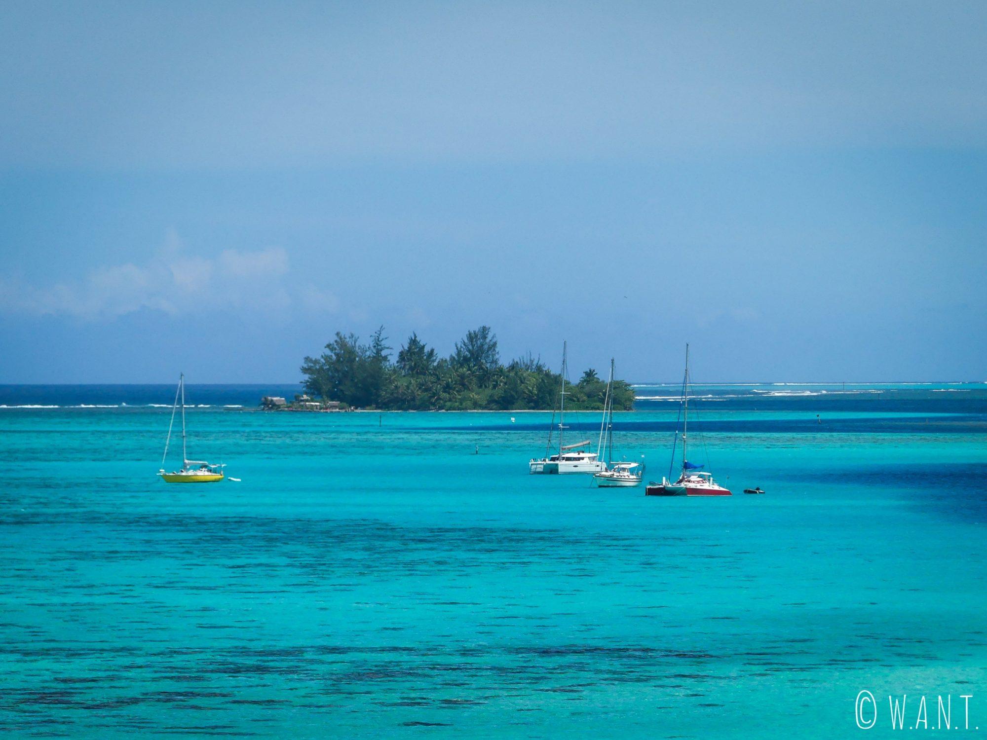 Un motu aux abords de l'île de Moorea, avec quelques bateaux de plaisance