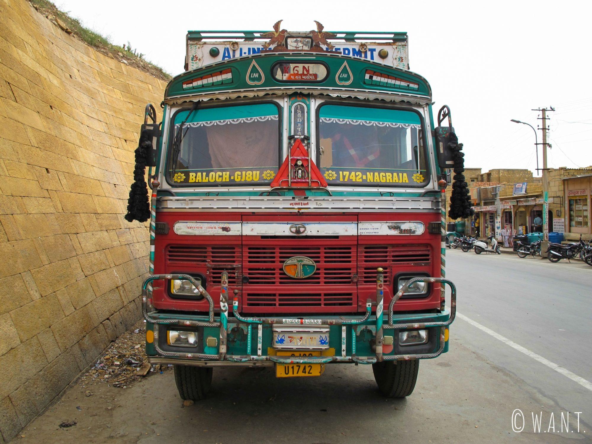 Face avant d'un camion benne Tata, aux multiples couleurs et ornements sacrés