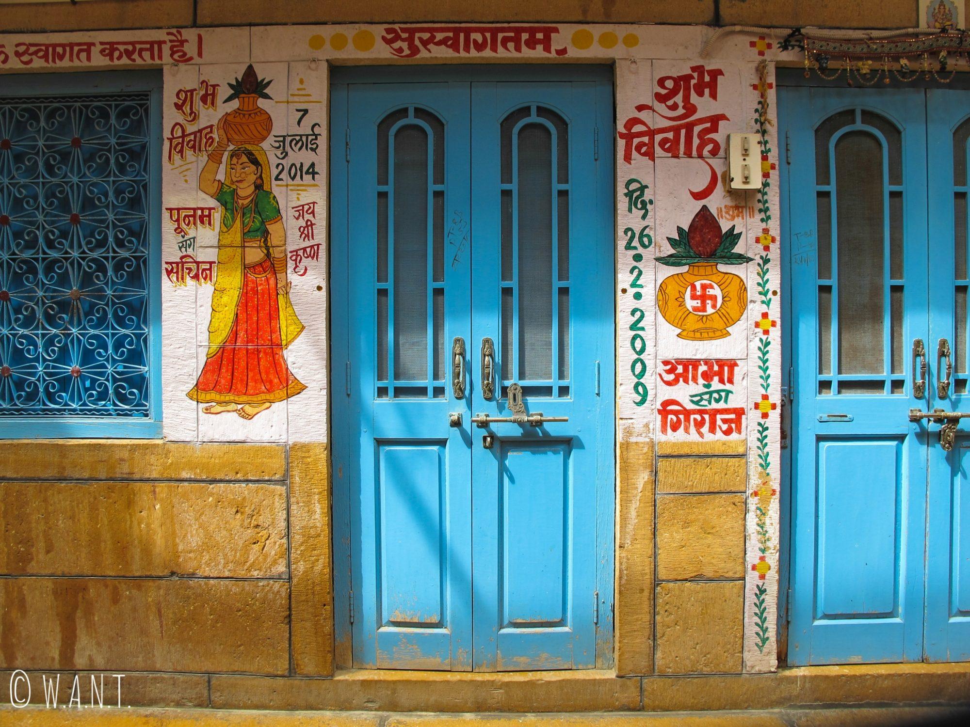Peinture représentant une femme porteuse d'eau à l'entrée d'une maison dans les rues de Jaisalmer