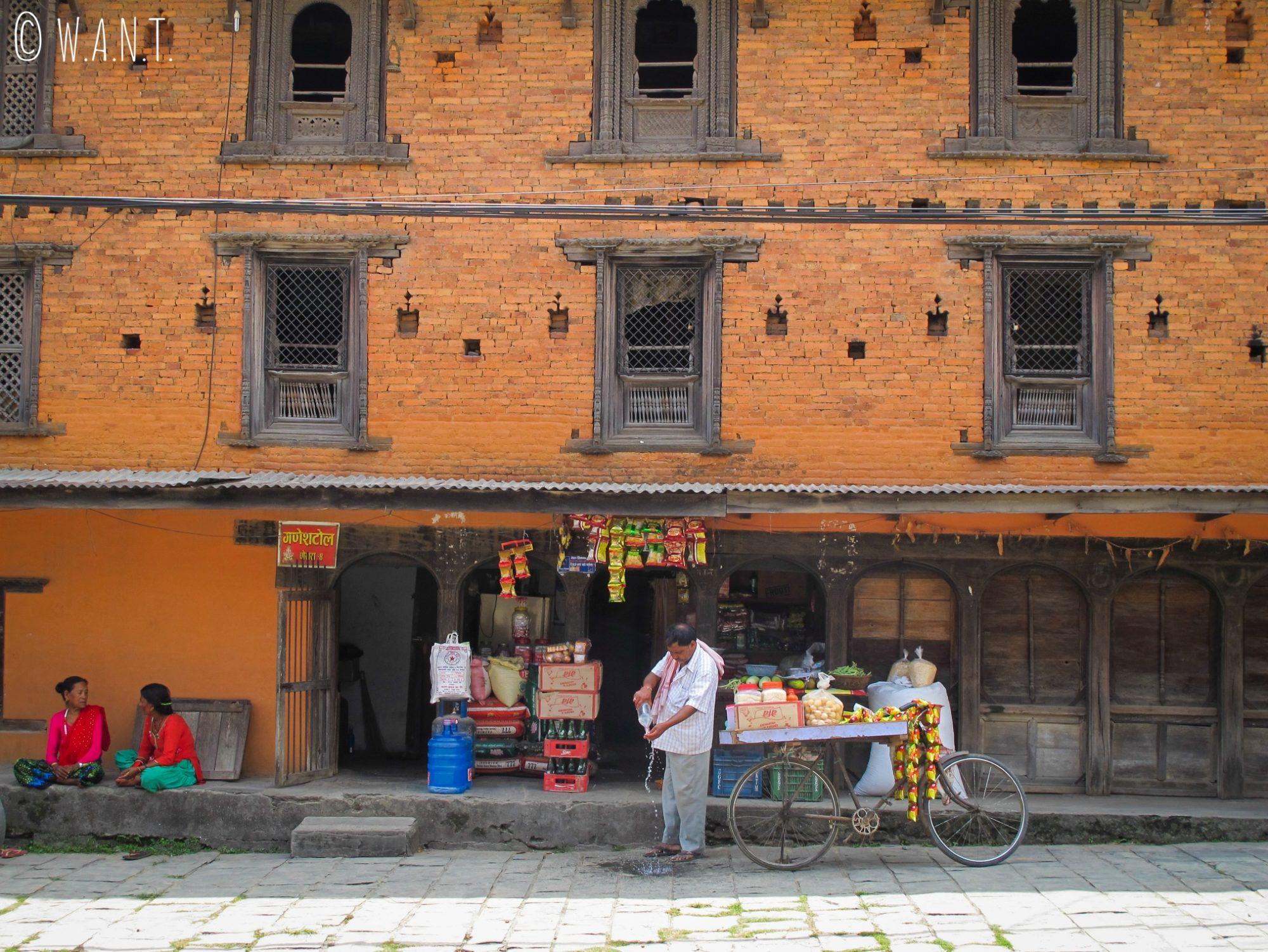 Façade d'une bâtisse dans le vieux Pokhara et marchand ambulant