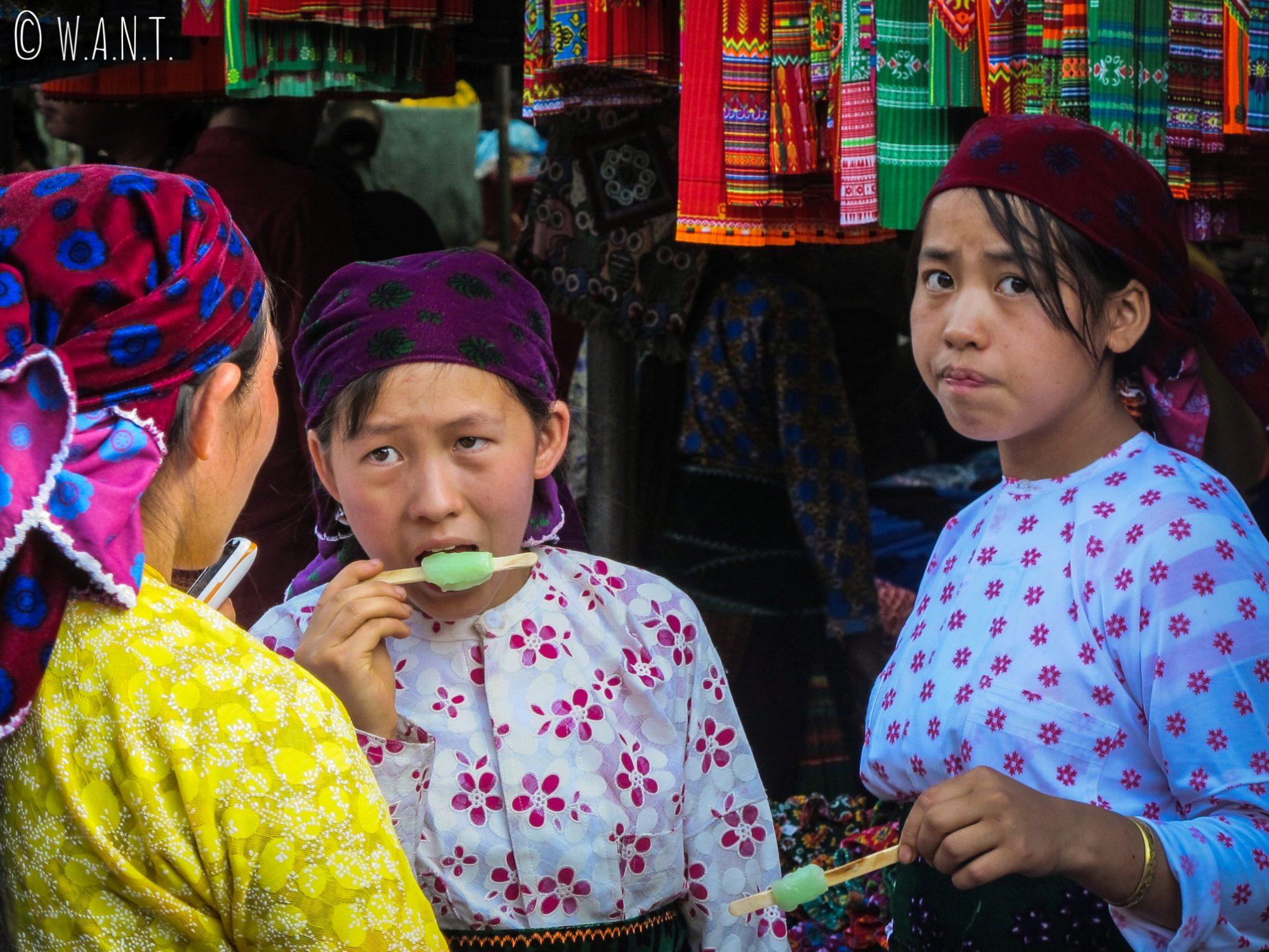 Les enfants sont nombreux à dévorer des glaces à l'eau sur le marché de Dong Van