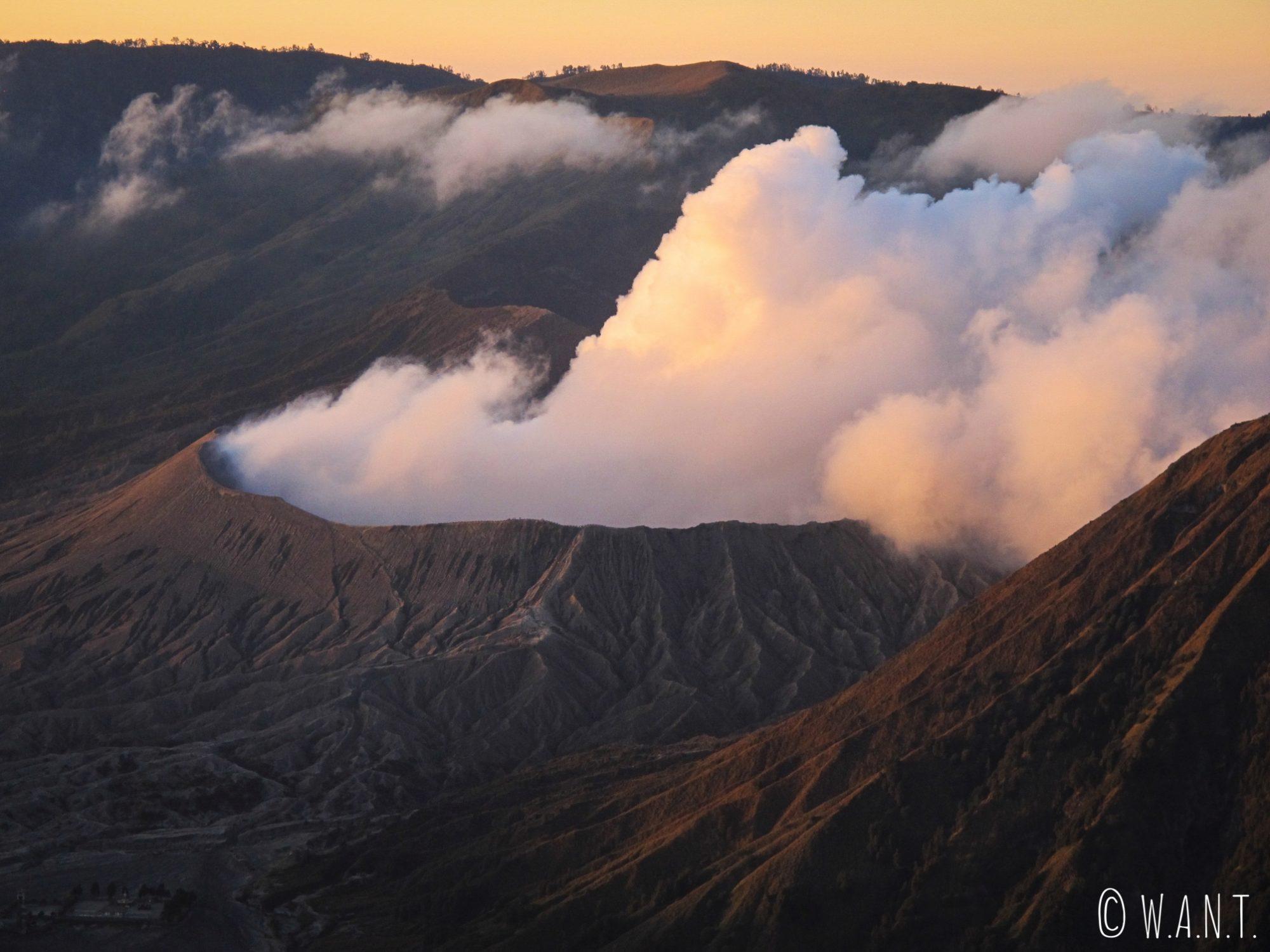 Gros plan sur le cratère fumant du Bromo au lever de soleil