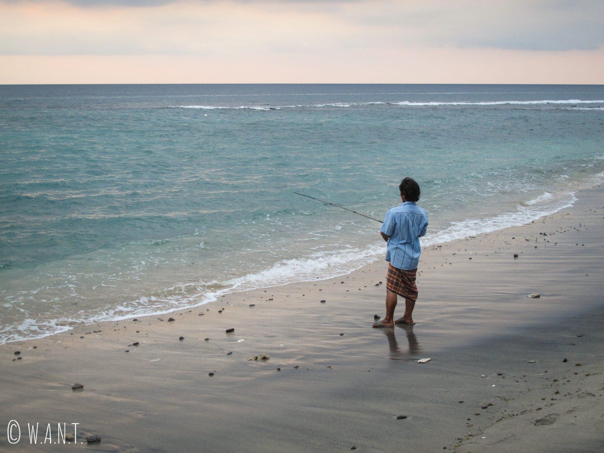 Pêcheur sur la plage de Mangsit à Lombok au coucher du soleil