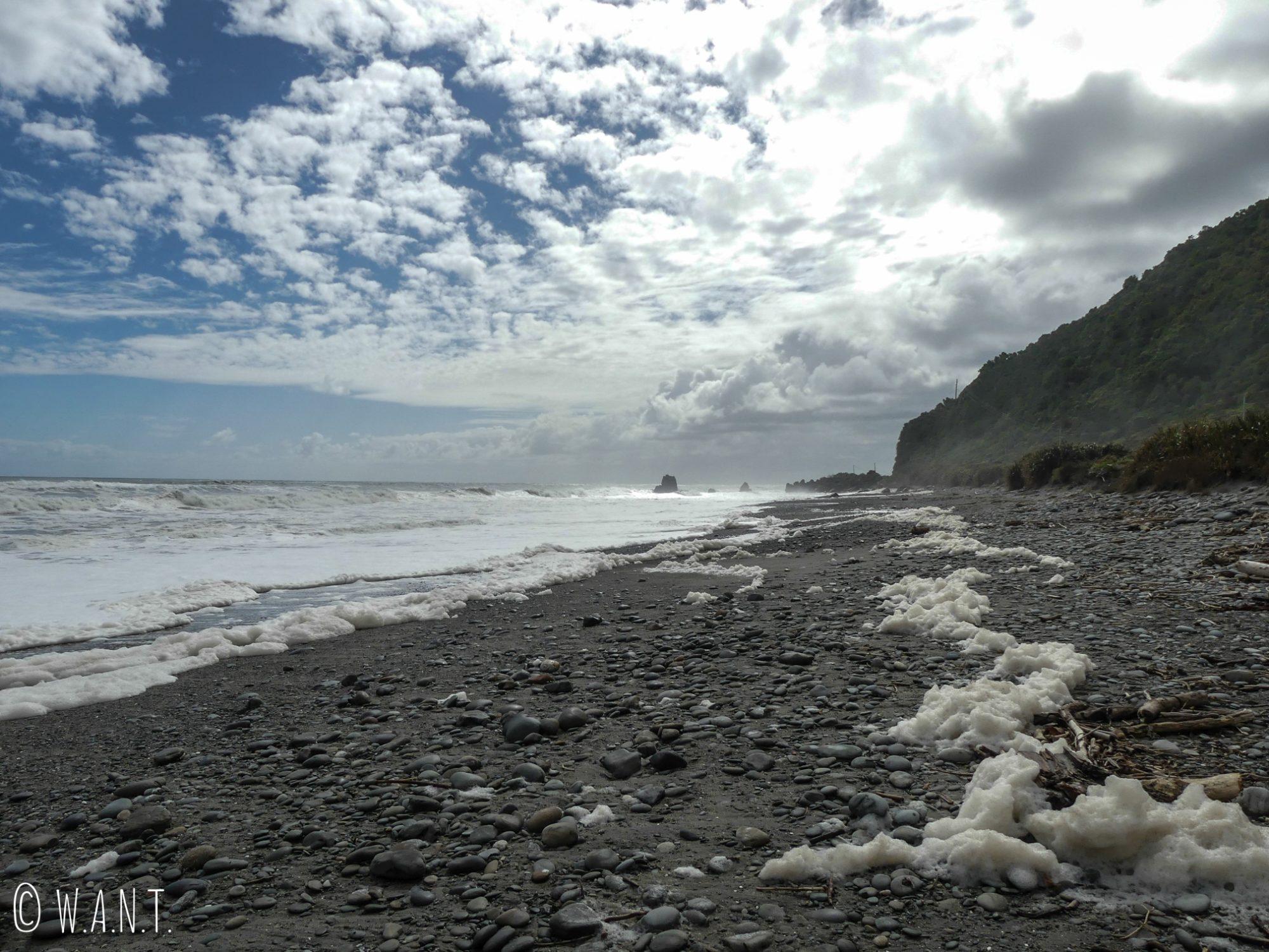 Écume le long de la plage à l'approche de Punakaiki en Nouvelle-Zélande